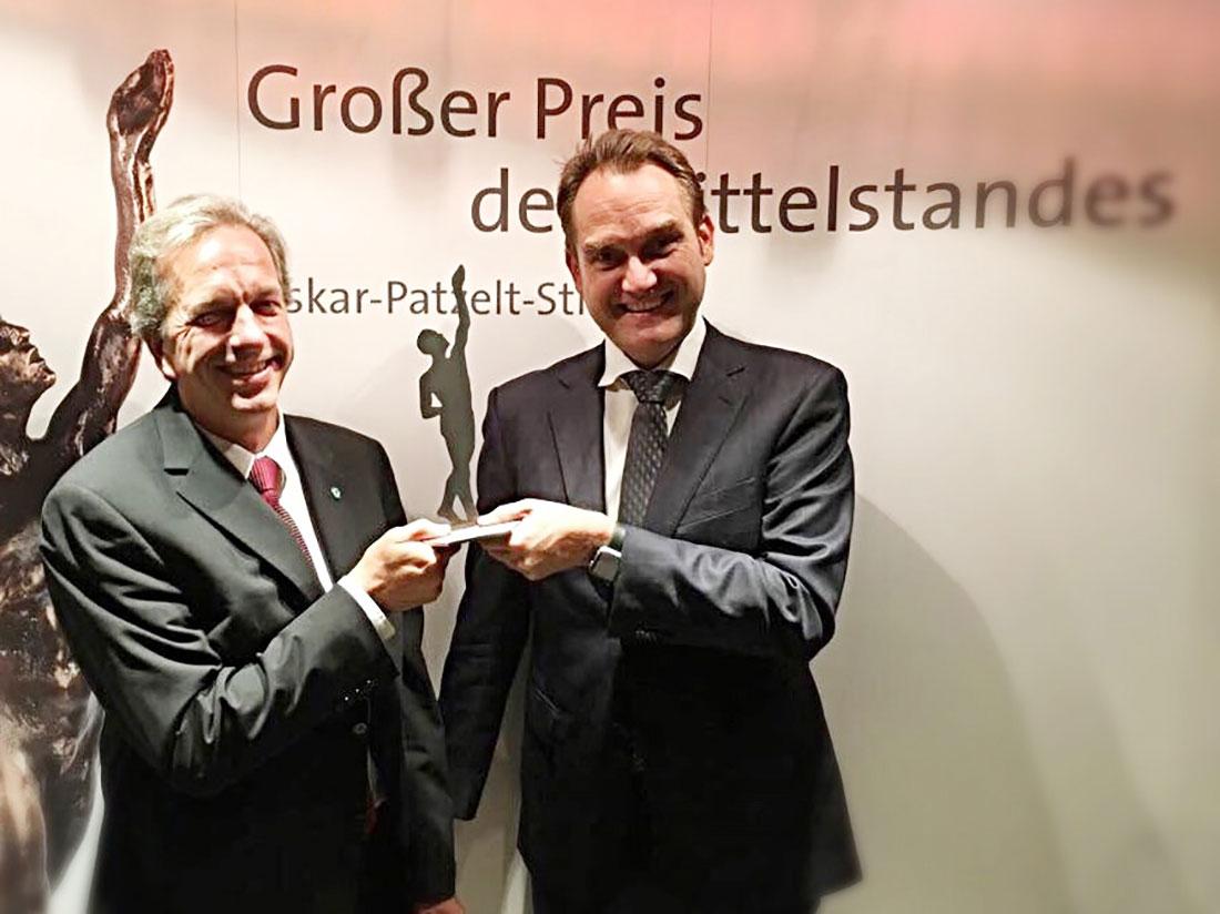 """Dirk Hönscheid (links) und Oliver Grün (rechts) mit der Preisträgerstatue als Finalist des """"Großer Preis des Mittelstandes""""."""