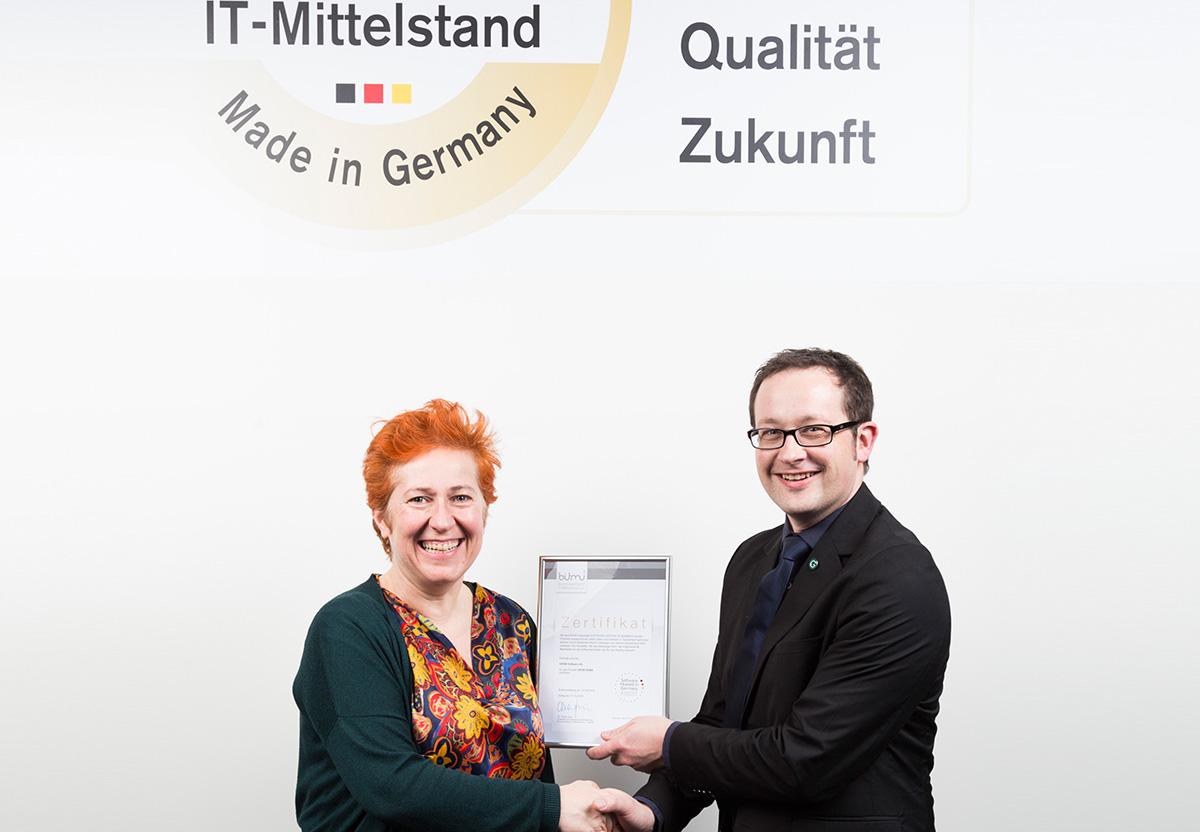 """Unser Kollege Michael Wessels (rechts) nimmt die Gütesiegel """"Software made in Germany"""" und """"Software hosted in Germany"""" von BITMi-Vizepräsidentin Andrea Gadeib in Empfang."""